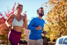 Young Man And Woman Jogging At...