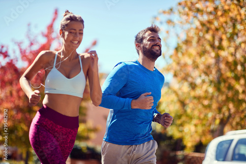 Fototapeta Young man and woman jogging at the park. healthy lifestyle. obraz