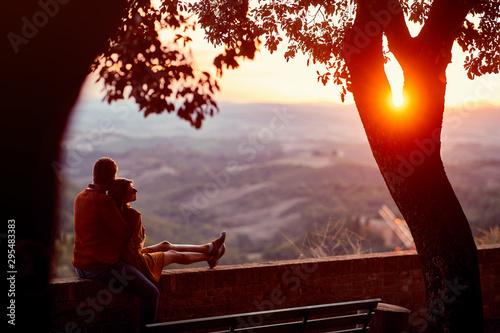 Obraz Loving man and woman  enjoying together on romantic sunset. - fototapety do salonu