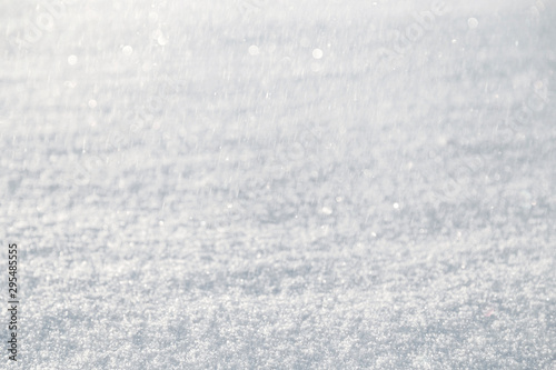 Close-up of fresh snow on the ground and blurred snowfall with bokeh on a sunny day Wallpaper Mural