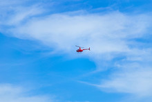 Red Helicopter Flying In The Sky. Small Red Helicopter In The Blue Sky