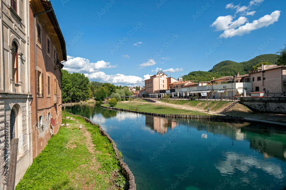 Fototapeta Rieti, city of central Italy. Velino river with old houses and geese that swim,