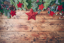Christmas Background With Fir Tree Branches And Red Stars Decorations On Wooden Table.