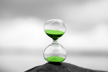 Green Hourglass Against A Blurred Background In Nature