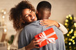 canvas print picture - Thankful afro woman with christmas gift hugging husband at home