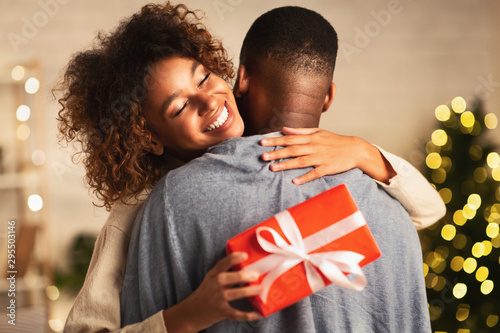 Photo Thankful afro woman with christmas gift hugging husband at home