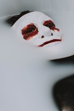 Vertical Selective Shot Of A White Masked Person With Bloody Red Eyes And Lips.