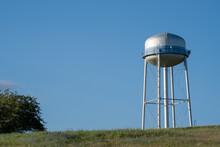 Watertower In A Field Against A Blue Sky.