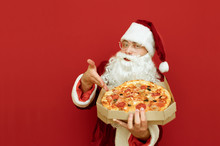 Handsome Santa Claus Pizza Deliveryman Isolated On Red Background With Pizza Box In His Hands Shows His Hand In Hot Tasty Pieces And Looks Into The Camera. Santa Delivers Pizza For Christmas.