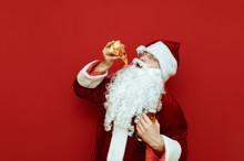 Cheerful Santa Claus With A Piece Of Pizza And A Bottle Of Beer In His Hands Stands On A Red Background,looks Inthe Camera And Smiles. Man In Santa Costume Eating Pizza And Drinking Beer, Having Fun