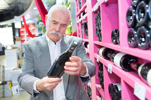 Photo  senior checking wine bottle at the supermarket