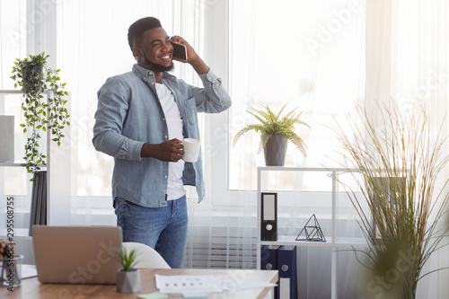 Fotografía  Businessman with coffee and cellphone standing near window in office