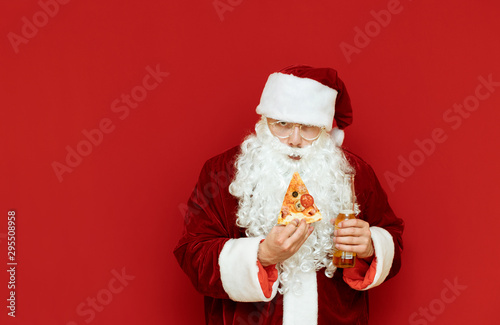 Cuadros en Lienzo Portrait of an evil Santa Claus drinking alcohol on a red background with a beer bottle and a piece of pizza in his hand,with an evil face looking into the camera