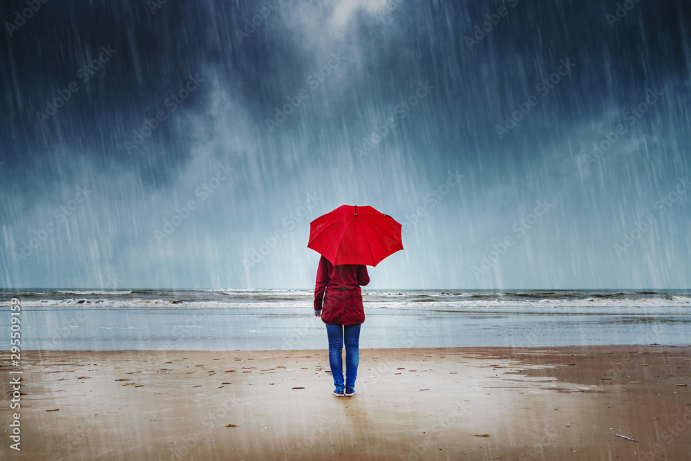 Fototapeta Lonely woman with red umbrella is standing in the rain watching the sea