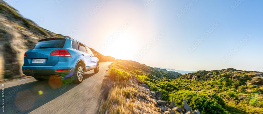 Fototapeta SUV car in spain mountain landscape road at sunset