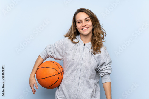 Young blonde woman with ball of basketball