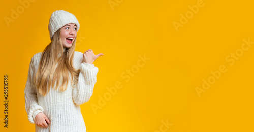 Fototapeta Cheerful girl pointing with thumb at empty space obraz