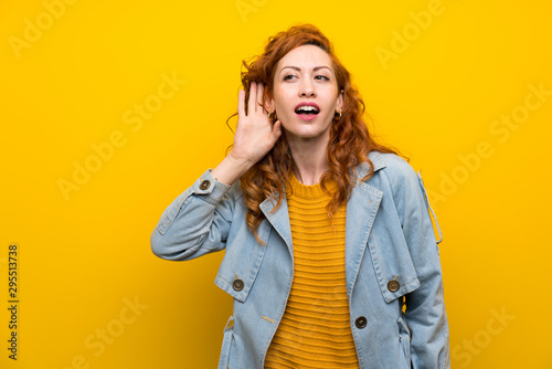 Redhead woman over isolated yellow background listening something Fototapete
