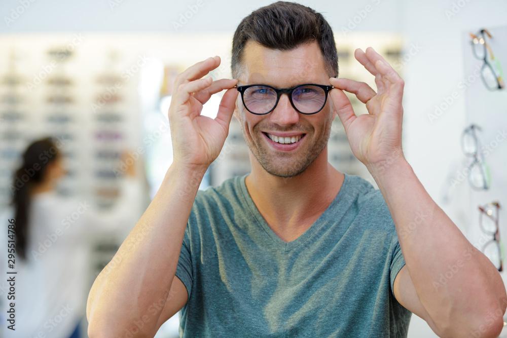 Fototapeta smiling man wearing eyeglasses in optical shop