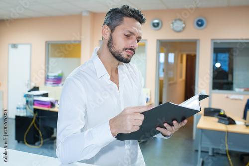Fotografía man in office reading file