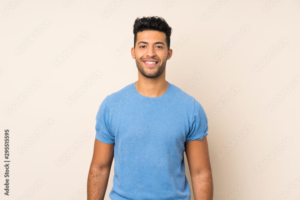 Fototapeta Young handsome man over isolated background keeping the arms crossed in frontal position