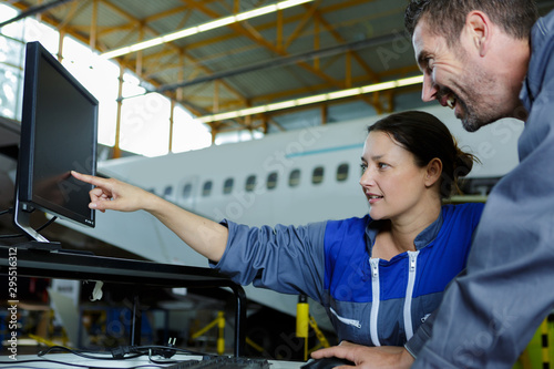 Poster Individuel female aircraft mechanic pointing at laptop