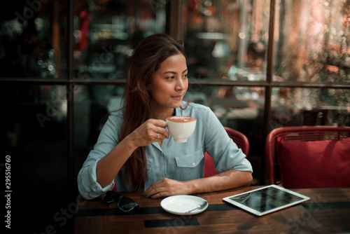 Photo sur Aluminium Cafe Asian woman drinking coffee in vintage color tone
