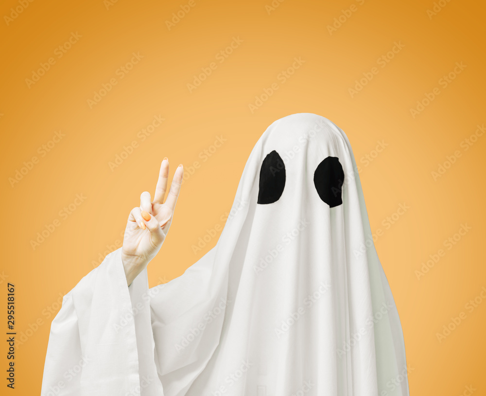 Fototapeta Halloween white ghost showing peace sign gesture on yellow background.