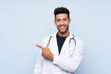 Young Doctor Man Over Isolated Blue Wall Pointing To The Side To Present A Product