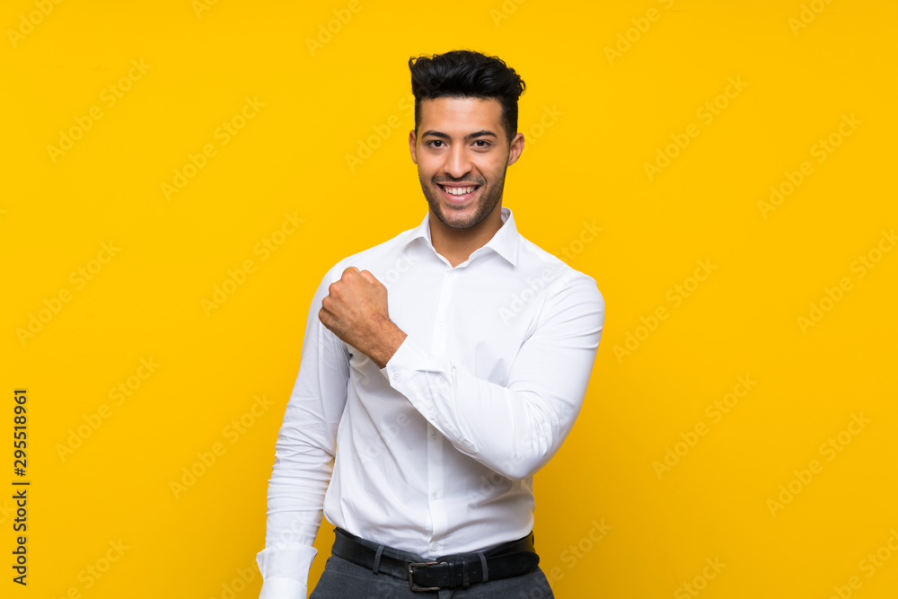 Fototapeta Young handsome man over isolated yellow background celebrating a victory