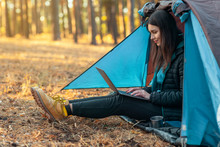 Young Girl Using Laptop In Camping Tent