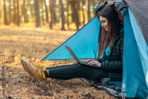 Obraz Young girl using laptop in camping tent - fototapety do salonu
