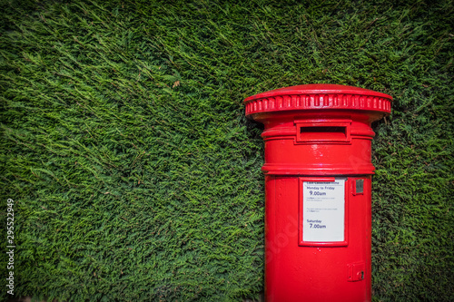 Fotomural  Classic Red British Pillar Box Against Hedge