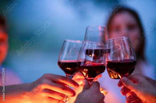 Fototapeta friends toasting red wine glass during french dinner party outdoor obraz