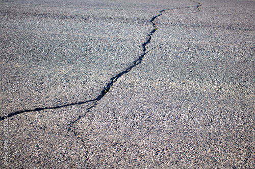 Fotomural  Cracked Asphalt on a Paved Road