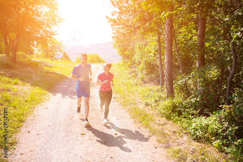 Spoed Foto op Canvas Jogging young couple jogging on sunny day at nature