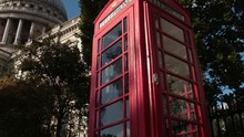 St. Paul's Cathedral Dome Revealed By Low Angle Pan Left Shot From A Classic English Telephone Booth While Birds Fly By