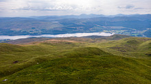 An Aerial View Of Grassy Mountain Slope With A Lake And Mountain Range In The Background Under A Cloudy Sky