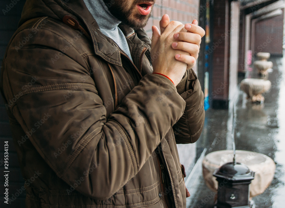 Fototapety, obrazy: handsome man standing on the street in winter time and warming his hands. cold day. it's raining. man in jacket. Town architecture on the background. Outdoors