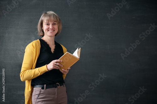Valokuvatapetti Teacher with textbook is standing near blackboard with copy space in a classroom