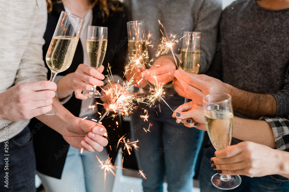 Fototapeta Group of friends holding flutes of sparkling champagne and burning bengal lights