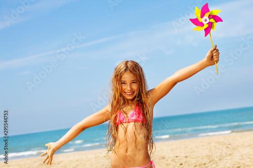 Obraz Happy girl smile in bikini on beach with pinwheel - fototapety do salonu