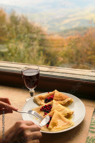 Pancakes with berries and tea on the mountain. Autumn at the window with wine and appetizer. Breakfast by the window in the fall. View of the mountains from the window of the house. Landscape on the m