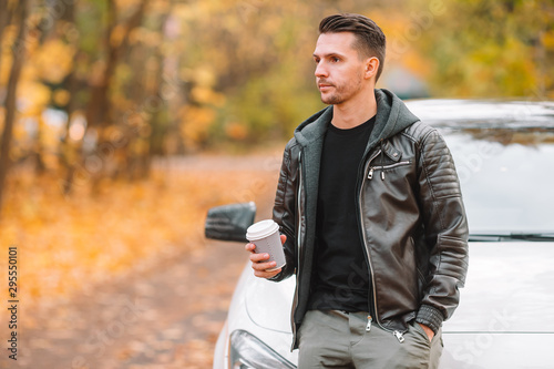 Cadres-photo bureau Ecole de Danse Young man drinking coffee with phone in autumn park outdoors