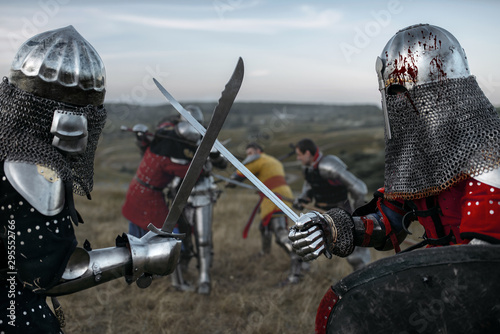 Photo Knights in armour and helmets fight with swords