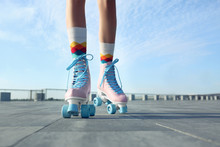 Young Woman With Vintage Roller Skates In City On Sunny Day, Closeup View