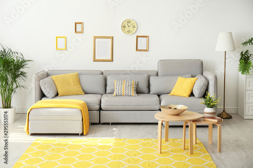 Obraz Stylish living room interior with comfortable grey couch - fototapety do salonu