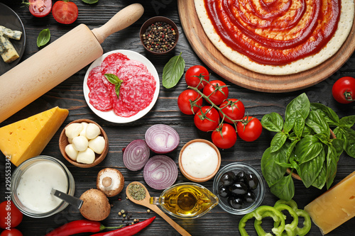 Obraz Flat lay composition with pizza crust and ingredients on dark wooden table - fototapety do salonu