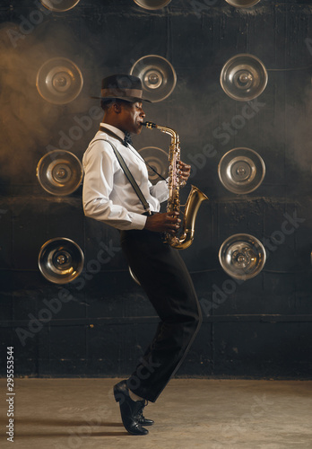 Photo Black jazzman in hat plays the saxophone on stage