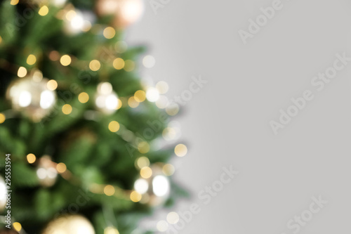 Arbre Beautiful Christmas tree with lights against grey background, blurred view. Space for text